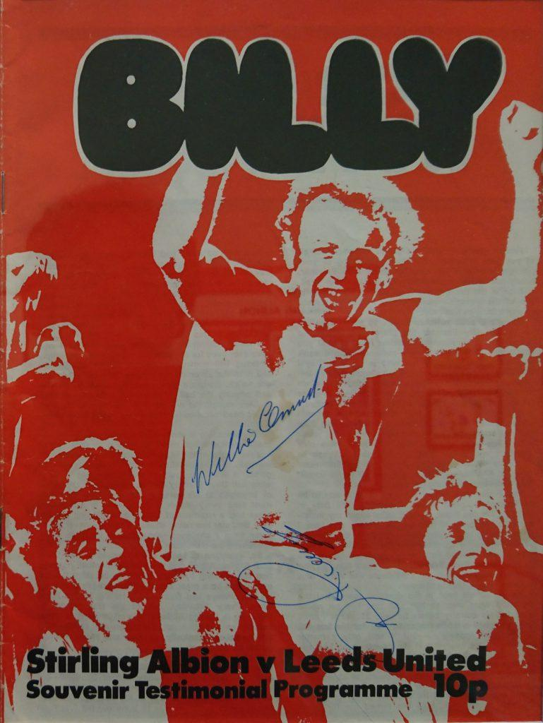 Football match programme with a picture of Billy Bremner on cover and signed by Billy Bremner. The Cover is mostly red and white.